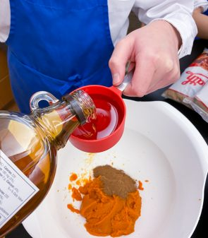 Measuring maple syrupto make Pumpkin Spice Granola Bars from Gather by David Robertson on eatlivetravelwrite.com