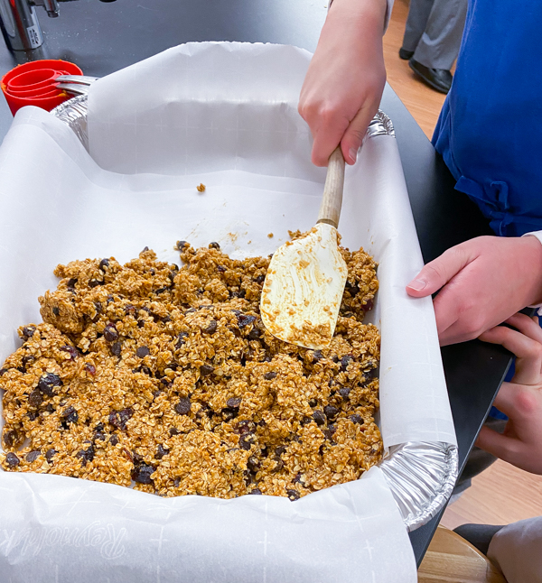 Pressing mixture into sheet pan making Pumpkin  Spice Granola Bars from Gather by David Robertson on eatlivetravelwrite.com