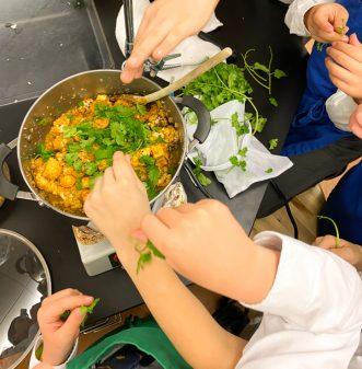 Kids adding cilantro to Jamie Oliver's Cauliflower Tikka Masala on eatlivetravelwrite.com