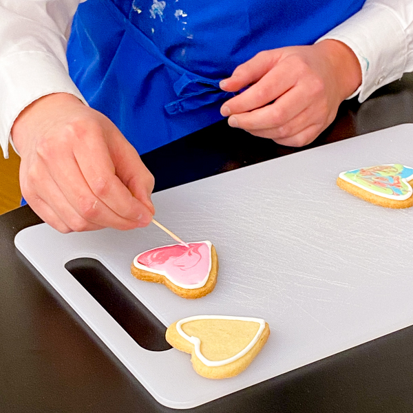 Using toothpicks to help flood icing for decorating sugar cookies with Adell Shneer on eatalivetravelwrite.com