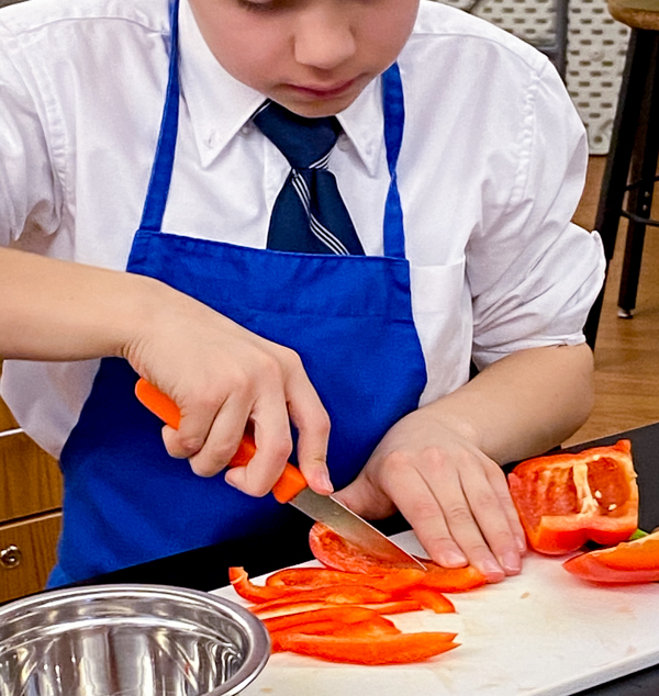 Kids slicing peppers to make fresh rolls with mango with Vanessa Yeung on eatlivetravelwrite.com