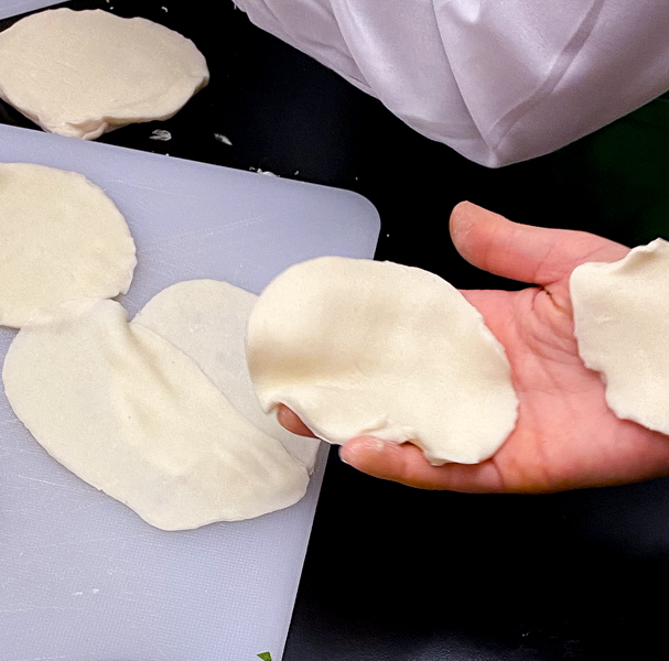 Prepping dumpling wrappers to make potstickers with Vanessa Yeung on eatlivetravelwrite.com