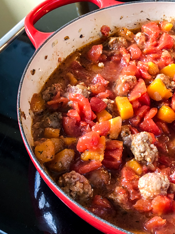 Adding canned tomatoes to the pot to make one pan pasta with vegetables and meatballs on eatlivetravelwrite.com
