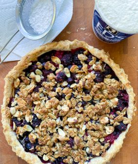 Mixed Berry Crumble Tart with icing sugar and ice cream
