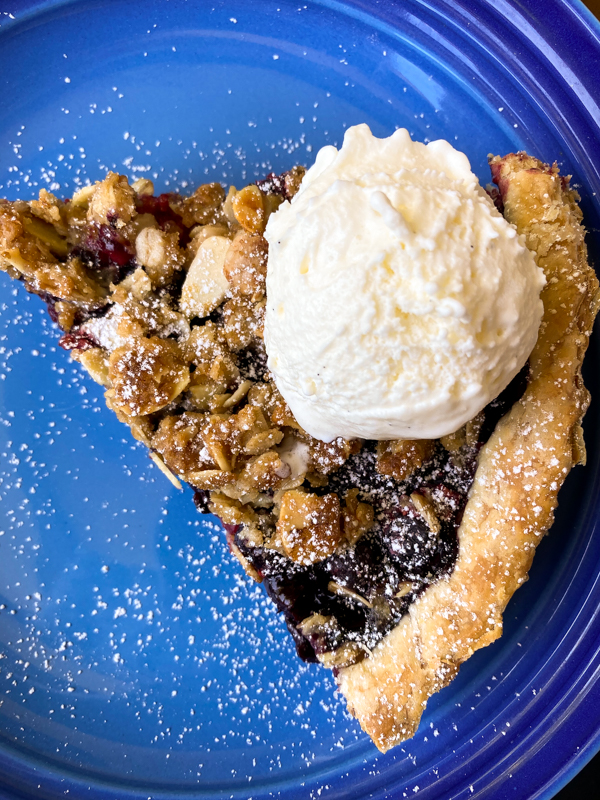 Slice of Mixed Berry Crumble Tart with ice cream