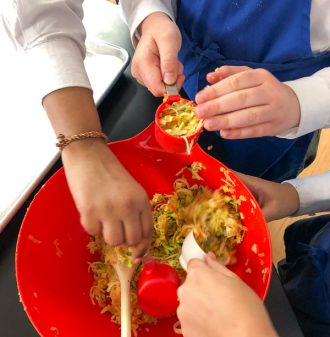 Kids in cooking club making veggie fritters