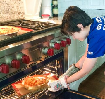 Kids putting a tomato quiche in the oven