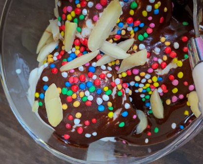 Ice cream topped with Dorie Greenspan hot fudge sauce, almonds and sprinkles
