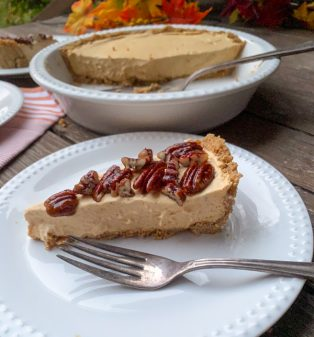 Slice of Frozen No-Bake Pumpkin Mousse Cheesecake with Caramelized Pecans on a plate