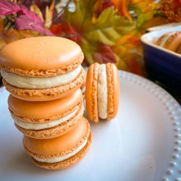A stack of Dorie Greenspan's Parisian Macarons on a white plate with autumn leaves in the background