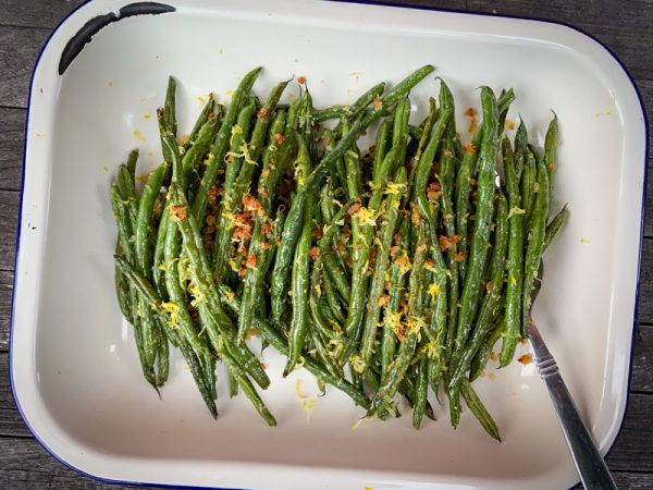 Overhead shot of Lemony green beans with crispy breadcrumbs and parmesan in an enamel dish