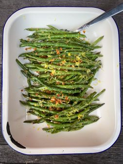 Overhead vertical shot of Lemony green beans with crispy breadcrumbs and parmesan in an enamel dish