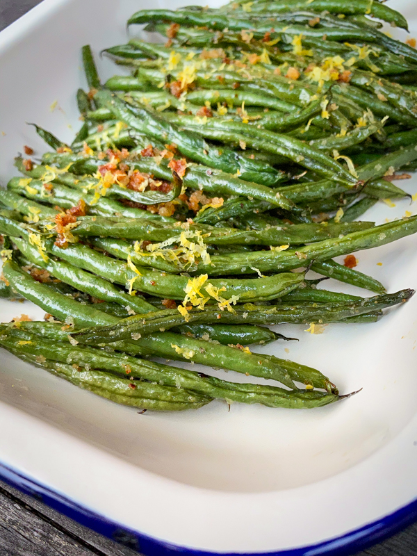 Closeup shot of Lemony green beans with crispy breadcrumbs and parmesan in an enamel dish