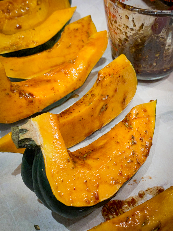 Acorn Squash Wedges ready for roasting on a baking tray