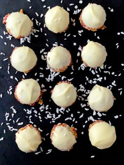 """Apricot, Coconut and Cranberry """"Truffles"""" topped with white chocolate on a black serving plate"""