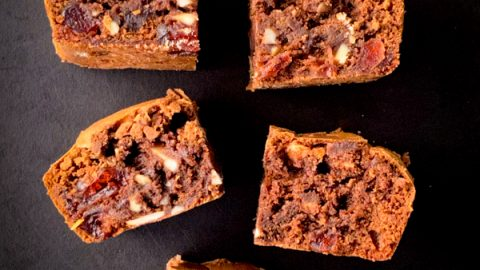 Chocolate Cherry and Almond Brownies sliced and served on a black plate