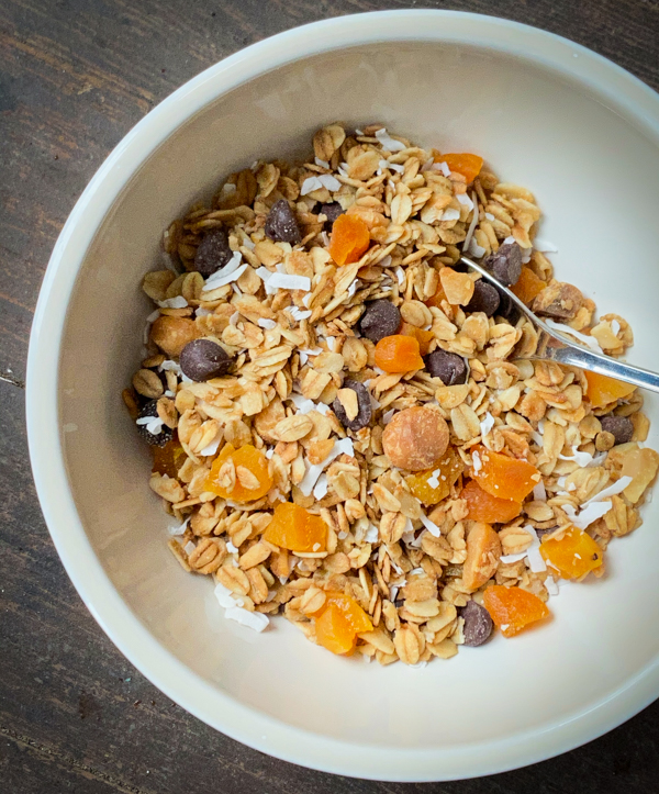 Apricot, coconut and macadamia granola with chocolate chips in a cream coloured bowl