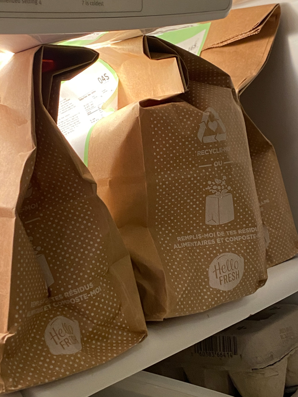 Hello Fresh meals in bags on a fridge shelf.