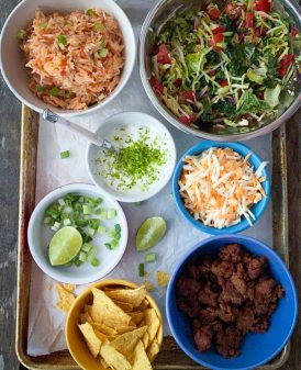 Ingredients for a veggie taco bowl laid out on a tray.