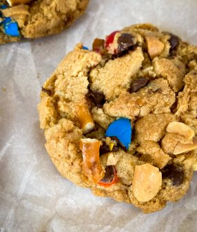 """Closeup of a """"Game Day"""" cookie with peanuts, M&Ms, pretzels and chocolate chips."""