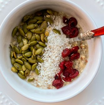 Oatmeal with pepitas, coconut and cranberries in a white bowl with a red handled spoon.