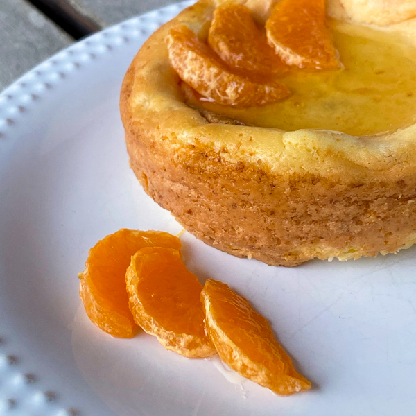 Side view of Tangerine-Topped Cheesecake on a plate with mandarine segments.