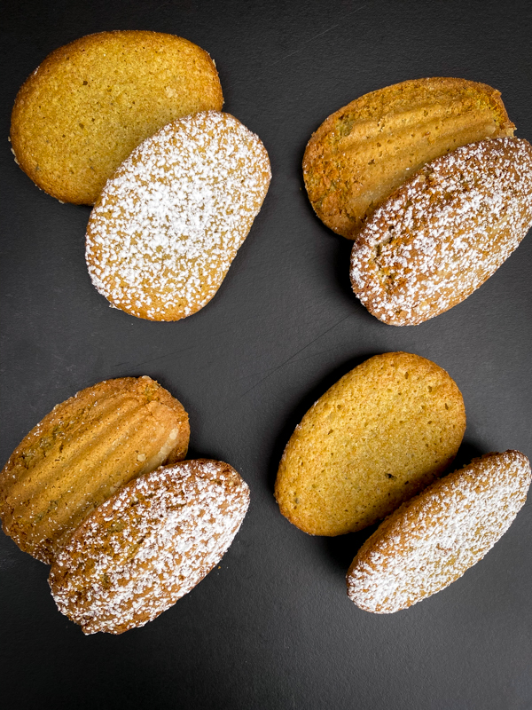 Matcha white chocolate madeleines dusted with icing sugar on a black tray.
