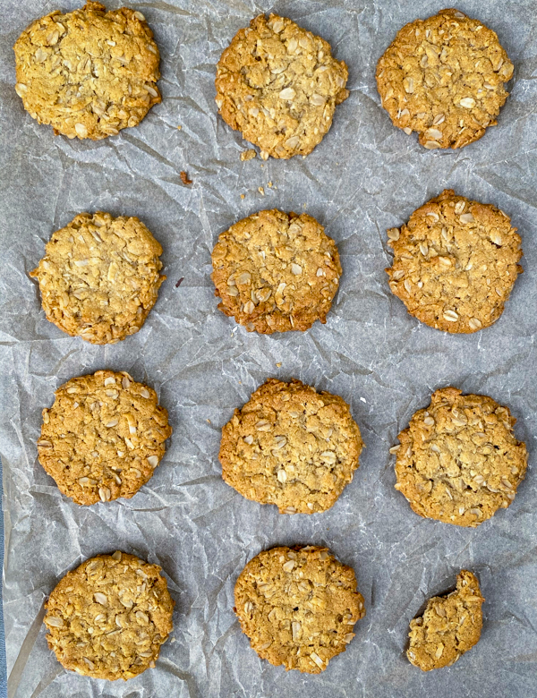 Gluten-free vegan ANZAC biscuits on parchment on a baking tray.