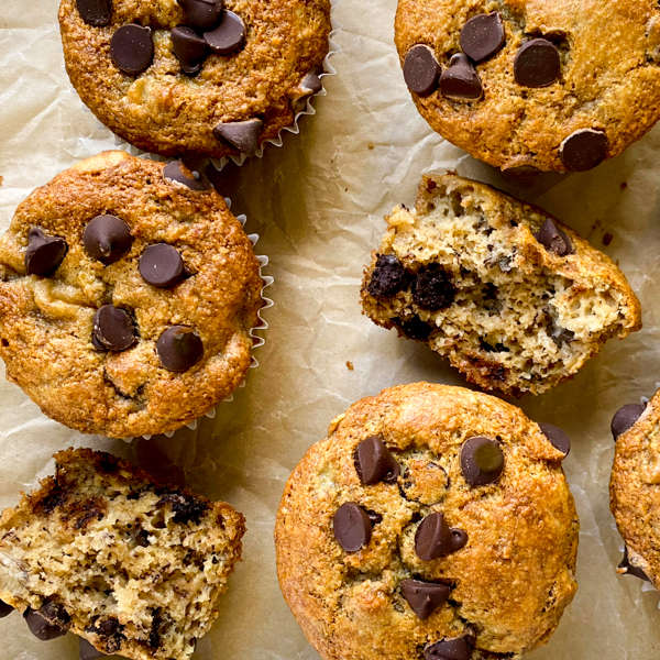 Gluten free almond and oat flour banana chocolate chip muffins on a bking tray with one cut open to see the insides.