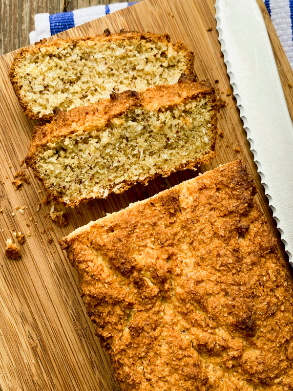 Almond and coconut breakfast loaf, sliced on a cutting board.