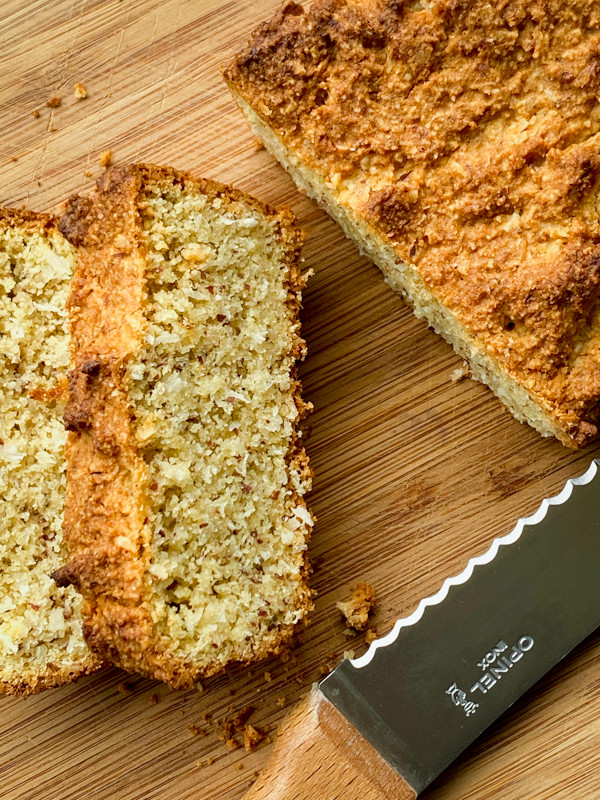 Slices of almond and coconut breakfast loaf on a cutting board with a knife.
