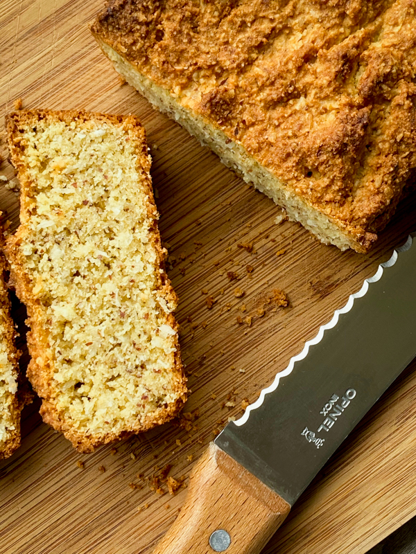 A slice of almond and coconut loaf on a cutting board.