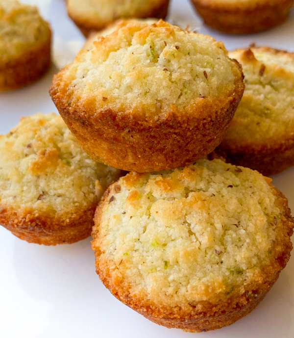 Small pile of Coconut lime financiers on a white plate.