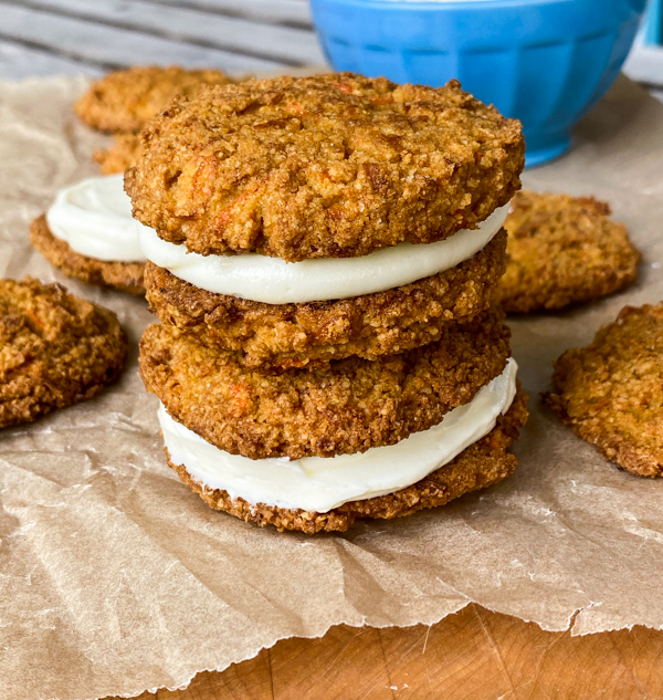 Gluten-free carrot cake cookies filled with cream cheese frosting on a sheet of parchment paper.