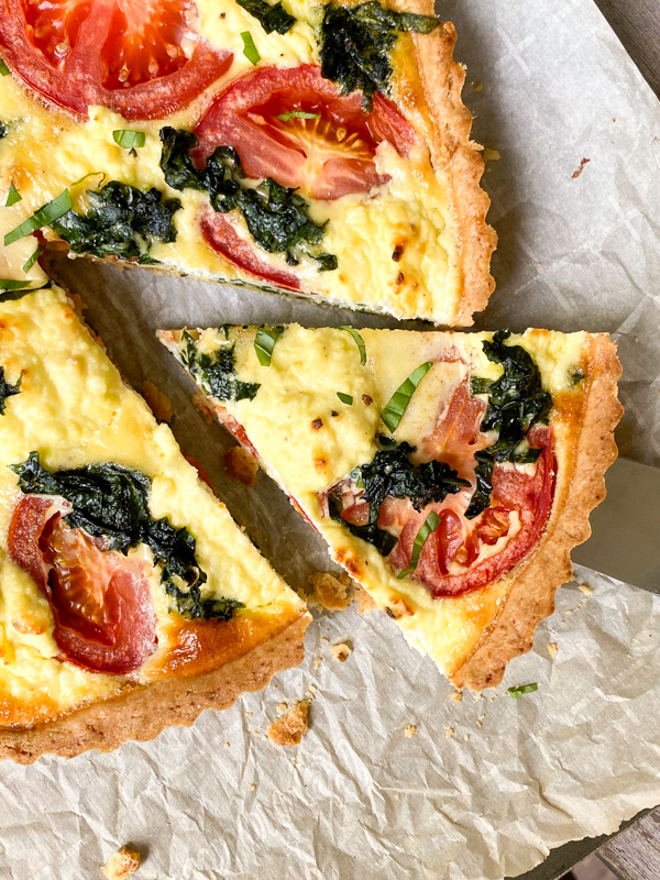 A slice of Dorie Greenspan's Tomato Tart with Mustard and Ricotta on a bking tray lined with parchment paper.