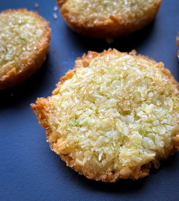 Close up of Coconut Patties from Dorie's Cookies on a dark blue serving tray.
