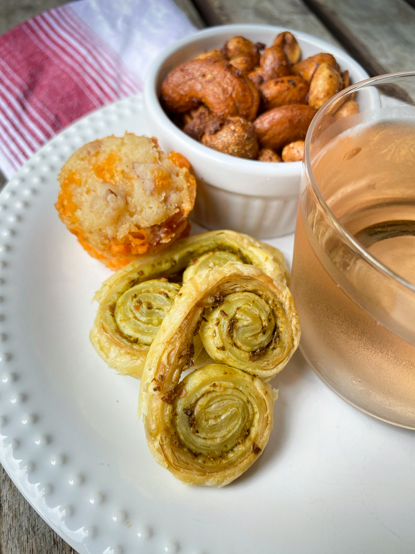 A selection of cocktail snacks with a glass or rosé on a white plate with a red and white napkin.