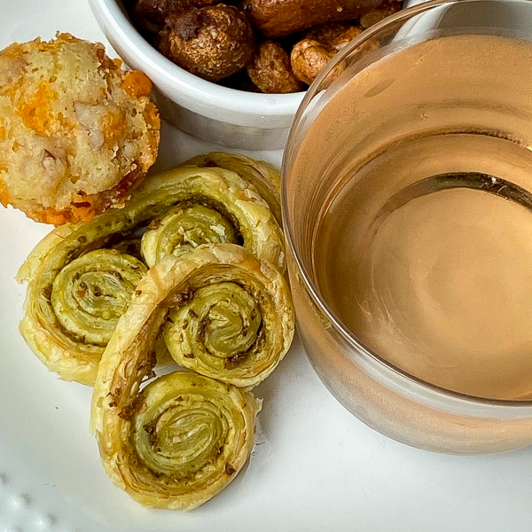 Closeup of Pesto Palmiers and a selection of cocktail snacks with a glass or rosé on a white plate with a red and white napkin.