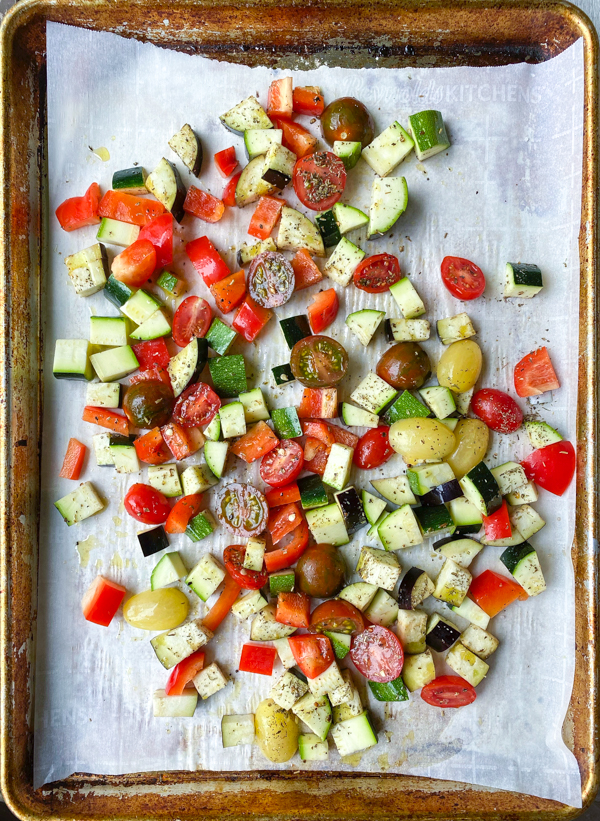 Vegetables ready to be roasted on a baking tray lined with parchment paper.