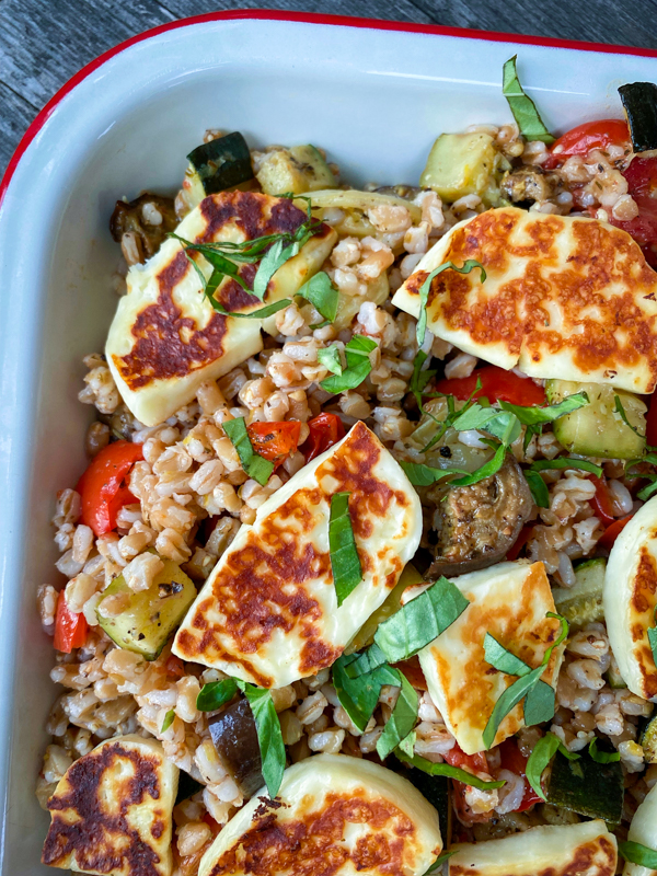 Close up of Farro with roasted vegetables and halloumi salad in a white enamel baking dish with a red rim.