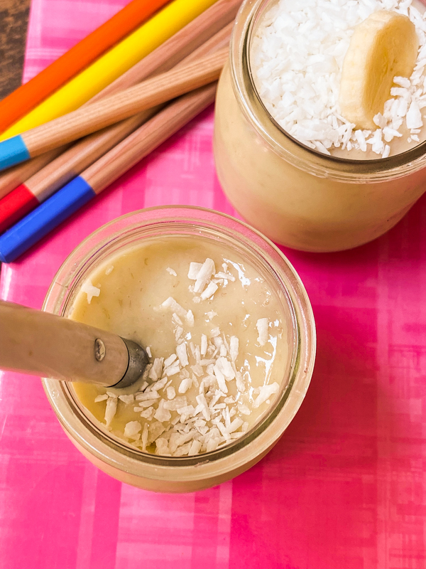 Top view of banana and coconut pudding in small glass jars on a notebook with coloured pencils.