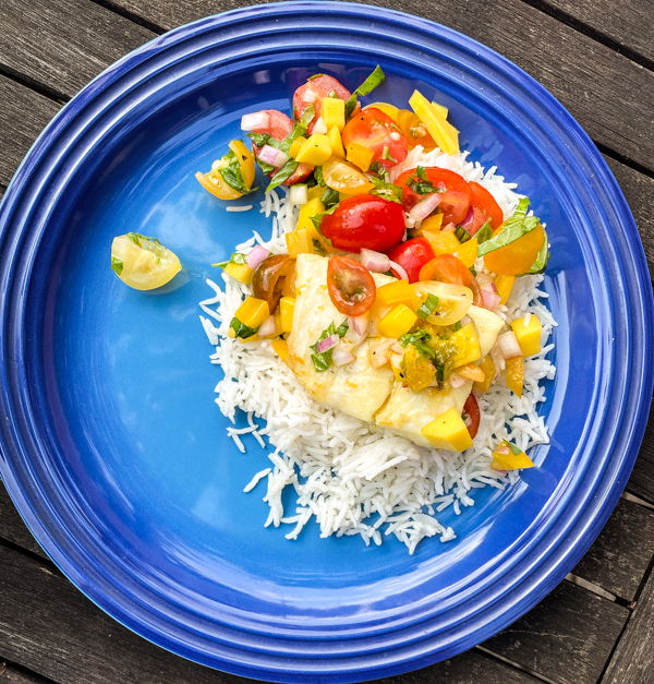 Plate of Citrus-Marinated Halibut with Mango Salsa on rice.