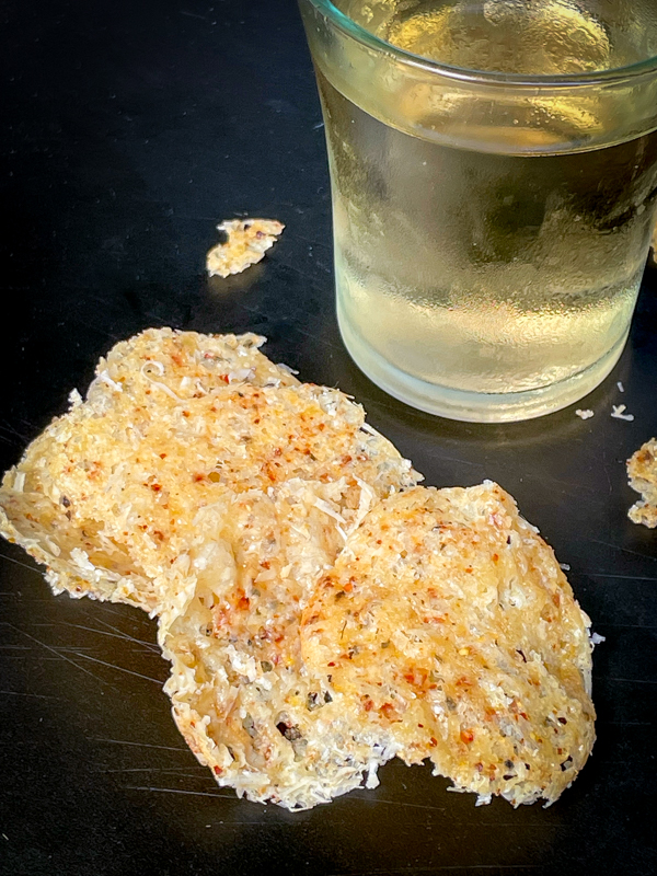 Cheese crisps and a glass of wine on a black serving tray.