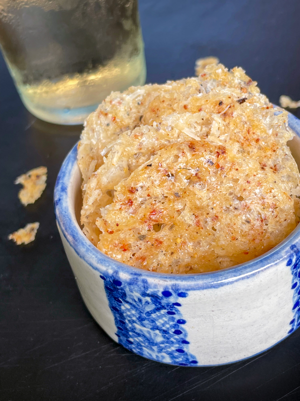 Cheese crisps in a small blue and white bowl with a glass of wine.