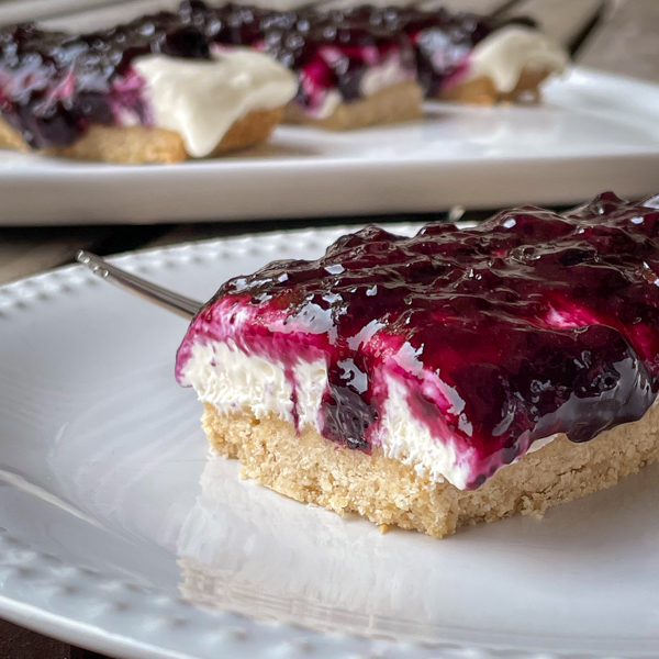 Blueberry cheesecake bars on a plate with a plate of bars behind it on a table.