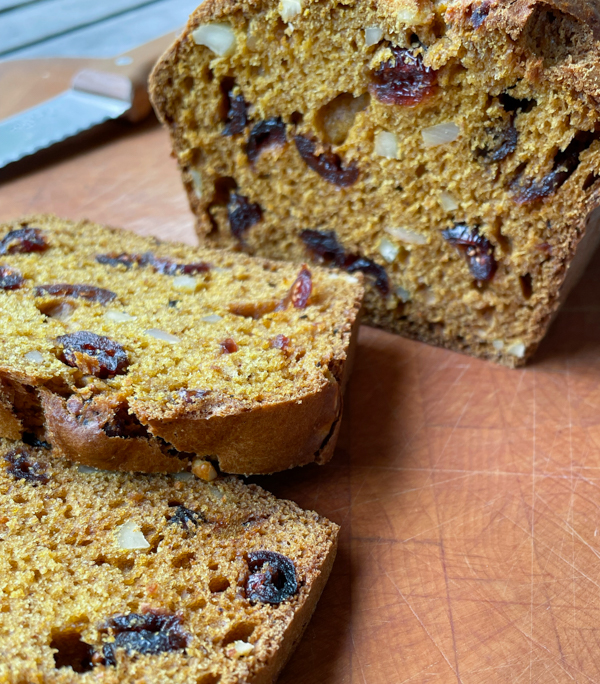 Cross section of pumpkin cranberry and almond loaf on a butting board.