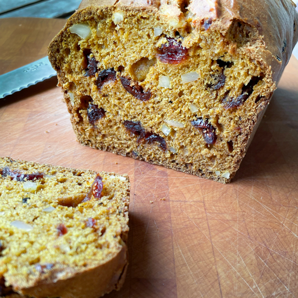 Pumpkin cranberry and almond loaf sliced on a cutting board.