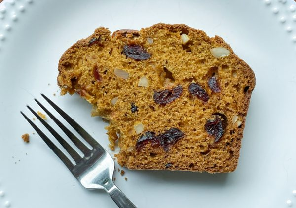 A slice of pumpkin cranberry and almond loaf on a white plate with a fork next to it.