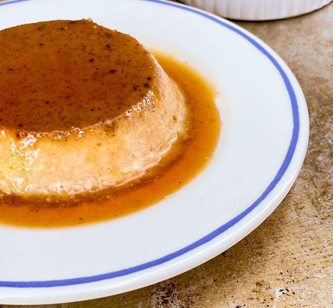 Pumpkin Crème Caramel on a plate surrounded with caramel sauce.