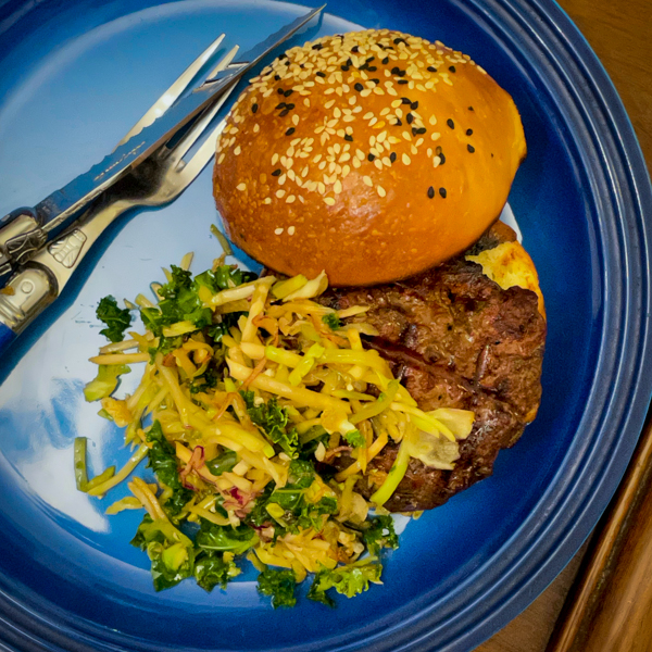 Dorie Greenspan's Umami burger on a blue plate with Asiam slaw.